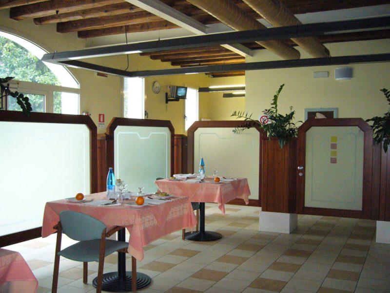 scorcio della sala da pranzo con tavole apparecchiate